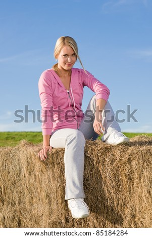 Portrait of sportive young woman relax sitting on hay bales - stock photo