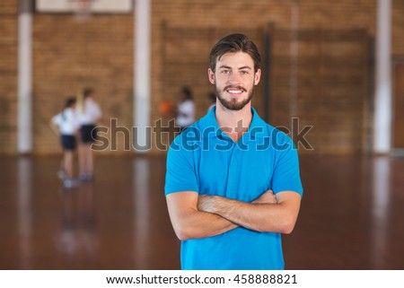 Portrait of sports teacher standing with arms crossed in basketball court at school gym