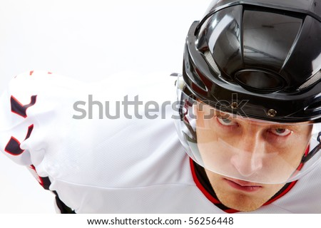 Portrait of sportsman in hockey uniform looking at camera with severe expression - stock photo
