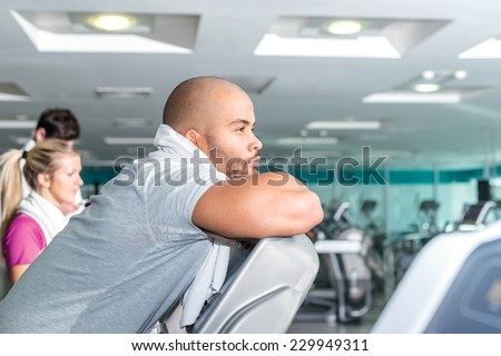 Portrait of sportsman in the gym. Young smiling man resting on a treadmill with a towel around his neck. - stock photo