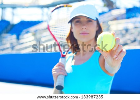 Portrait of sportswoman with focus on tennis ball. Horizontal shot.