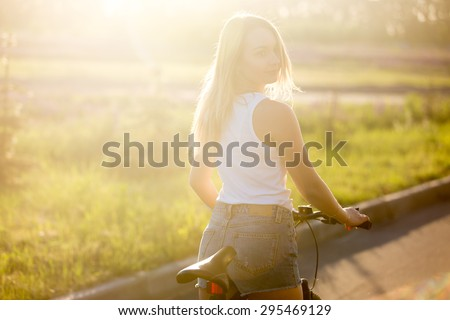 Portrait of sporty beautiful young woman starting bike ride wearing casual white tank top and jeans shorts on the street in bright sunlight on summer day - stock photo