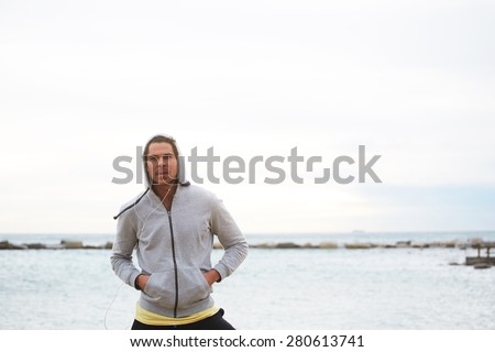 Portrait of sporty caucasian man resting during his training on the beach while listening to music with headphones, attractive male runner dressed in sweatshirt standing on sea horizon background - stock photo