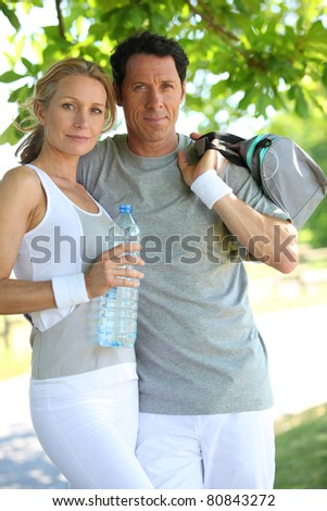 Portrait of sporty couple with bottle of water - stock photo