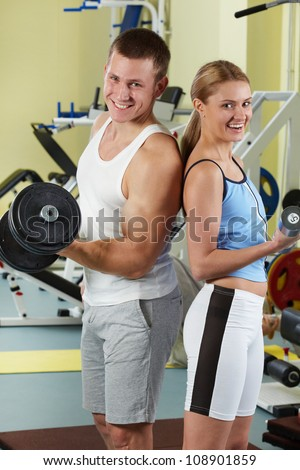 Portrait of sporty couple with dumbbells smiling at camera in gym - stock photo