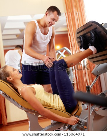 Portrait of sporty female doing physical exercise with young trainer helping her - stock photo