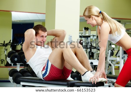 Portrait of sporty female helping handsome guy do physical exercise in gym - stock photo