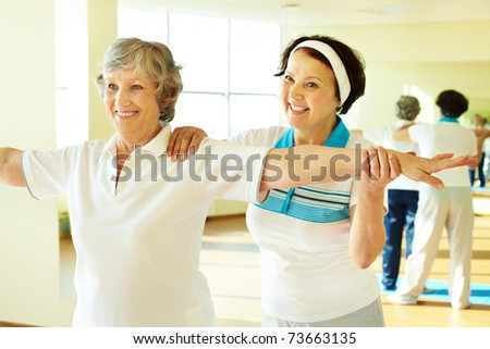 Portrait of sporty female supporting her friend while doing physical exercise in sport gym - stock photo