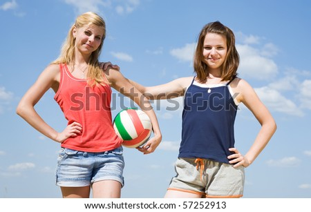 Portrait of sporty girls with volleyball on sand beach - stock photo