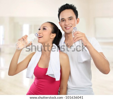 Portrait of sporty healthy young woman and man drinking water in the gym - stock photo
