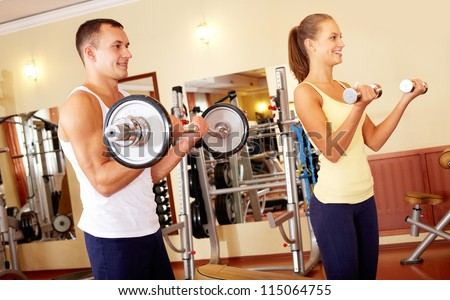 Portrait of sporty man and woman training with barbells - stock photo