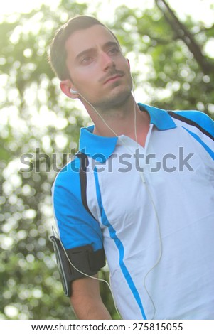portrait of sporty man wearing earphone to listening music during jogging - stock photo