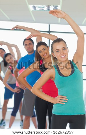 Portrait of sporty people doing power fitness exercise in row at yoga class - stock photo