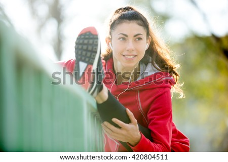 Portrait of sporty smiling woman doing hamstring stretch in park after jogging. Female athlete runner getting ready for running on the bridge. Fit girl enjoying workout. Active lifestyle concept - stock photo