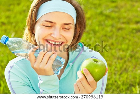 Portrait of sporty smiling woman with a water bottle and green apple on a grass background. outdoor sports. healthy sport lifestyle - stock photo