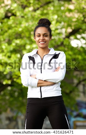 Portrait of sporty smiling woman with arms crossed standing outdoors