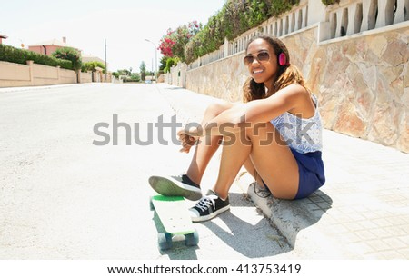 Portrait of sporty trendy african american teenager girl using headphones to listen to music, smiling with skateboard, outdoors. Adolescent technology lifestyle, home exterior suburban street. - stock photo