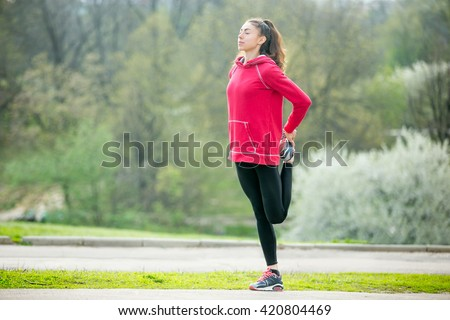 Portrait of sporty woman doing stretching exercises in park before training. Female athlete runner getting ready for running routine. Sport active lifestyle concept. Full length - stock photo