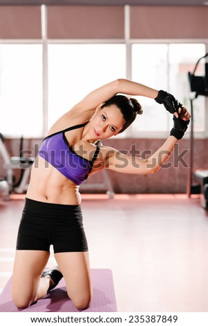 Portrait of sporty woman stretching her body