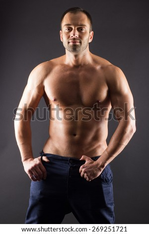 Portrait of sporty young muscular male topless shirtless athletic macho standing posing over black background. Torso of strong man in jeans against dark background. - stock photo