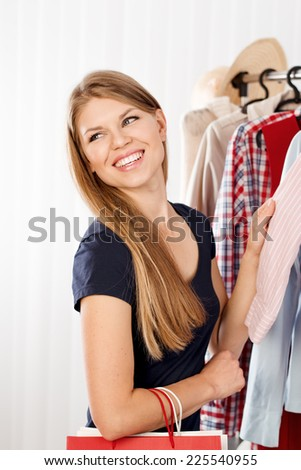 Portrait of spree shopper in retail store choosing dress to try. Young female shopaholic buying clothes in shopping mall. - stock photo
