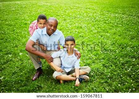Portrait of squatted father with two little sons on green lawn