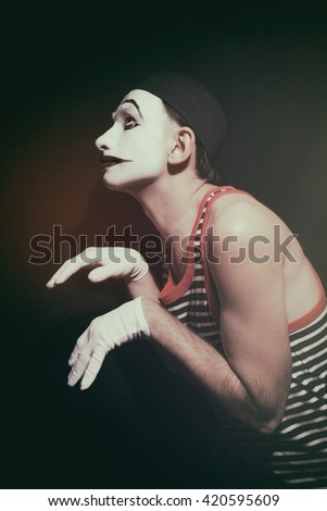 Portrait of stalking actor mime on a black background