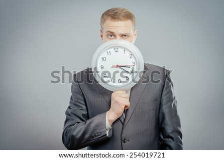 Portrait of standing businessman wearing suit and hiding his face behind clock