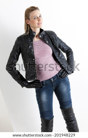 portrait of standing woman wearing jeans and black boots - stock photo
