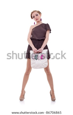 portrait of standing young woman with handbag posing - stock photo
