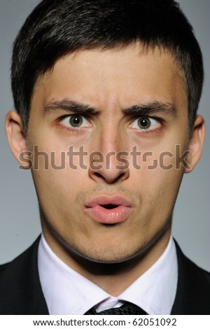 Portrait of stressed  business man in formal suit and black tie. gray background - stock photo