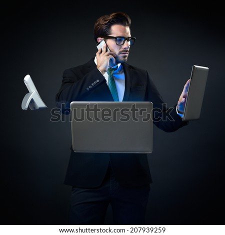Portrait of stressed businessman talking on phone surrounded by technology. Isolated on black. - stock photo