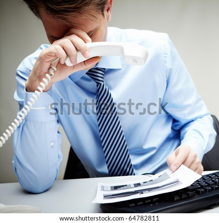 Portrait of stressed businessman with phone receiver in hand touching his head at workplace - stock photo