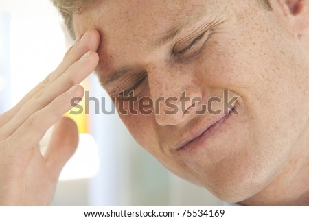 Portrait of stressed young businessman with hand on forehead - stock photo