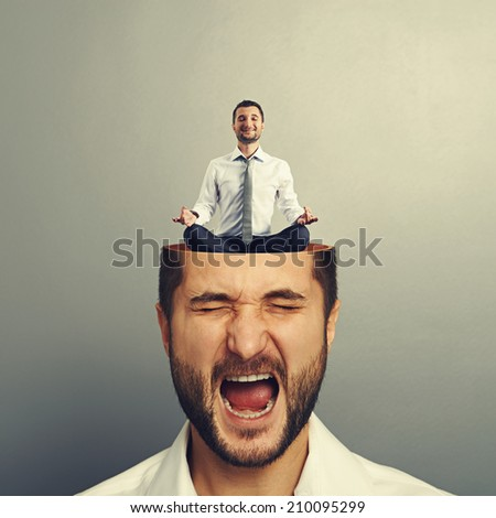 portrait of stressed young man with open head. calm businessman sitting in yoga asana and smiling in the man's head. photo over grey background - stock photo