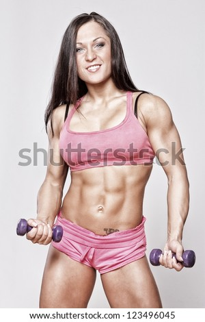 Portrait of strong and beautiful woman with muscles - stock photo