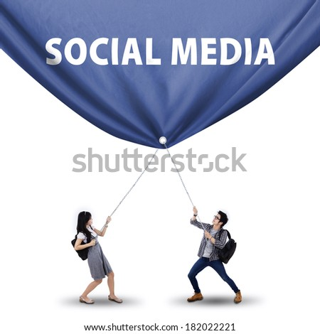 Portrait of student couple pulling a big banner of social media - stock photo