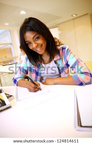 Portrait of student girl writing on notebook - stock photo
