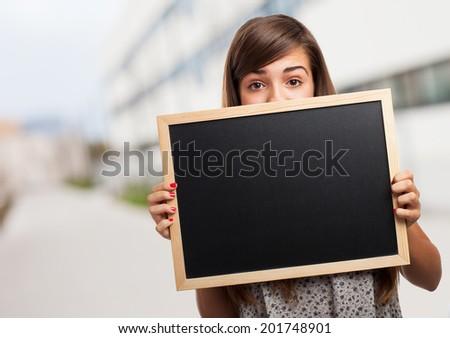 portrait of student hidden behind a chalkboard - stock photo