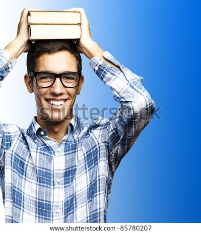 portrait of student with books on the head against a blue background - stock photo