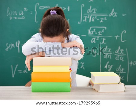 Portrait Of Student With Head Down On Stack Of Books - stock photo