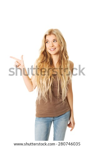 Portrait of student woman pointing to the right. - stock photo