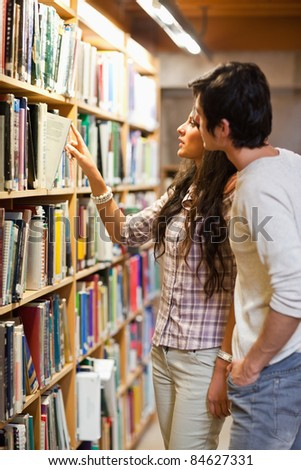 Portrait of students choosing a book in a library - stock photo