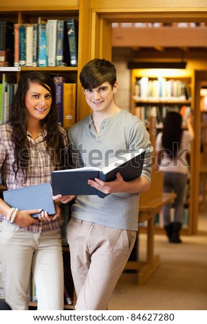 Portrait of students holding blue books in a library - stock photo