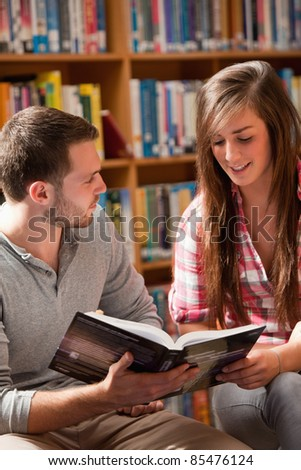 Portrait of students reading a book in a library