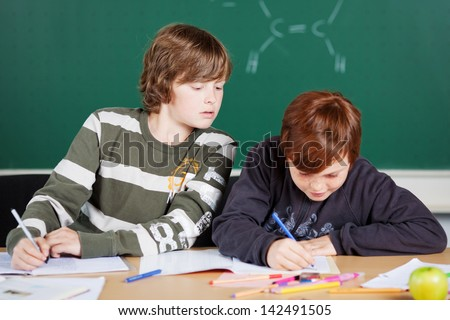 Portrait of students sitting and writing their notes inside the classroom - stock photo