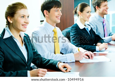 Portrait of students sitting at the table in row at seminar - stock photo
