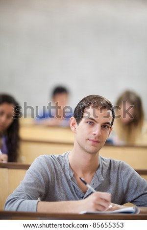 Portrait of students taking notes in an amphitheater with the camera focus on the foreground - stock photo