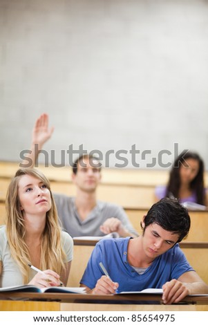 Portrait of students taking notes while their classmate is raising his hand in an amphitheater - stock photo