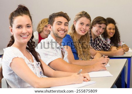 Portrait of students writing notes in classroom
